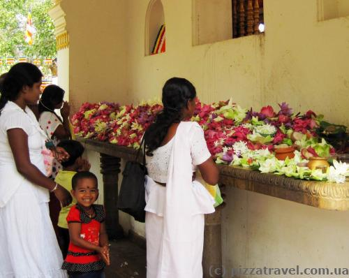 Locals bring lotus flowers and lay them on the altar.